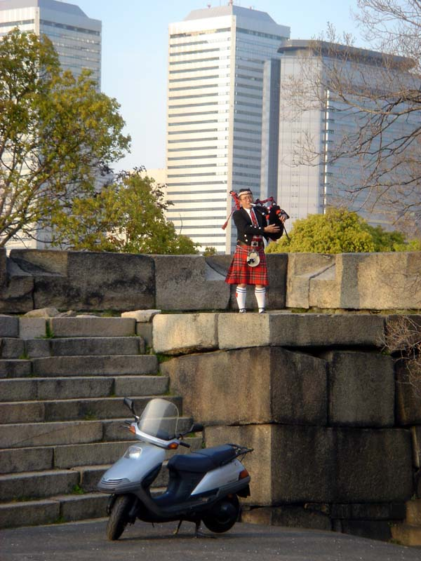 A Japanese man playing bagpipes wearing a kilt in the middle of Osaka.  Your guess is as good as mine.