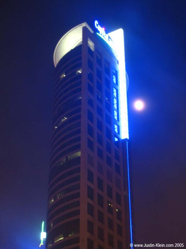 The moon next to a particularly cool-looking building in Shanghai