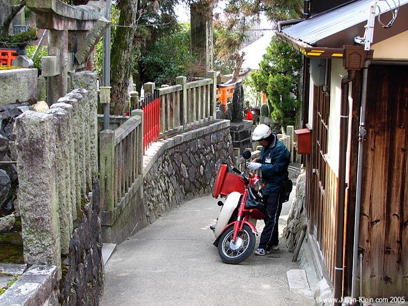 The mailman double-checks his delivery in Kyoto