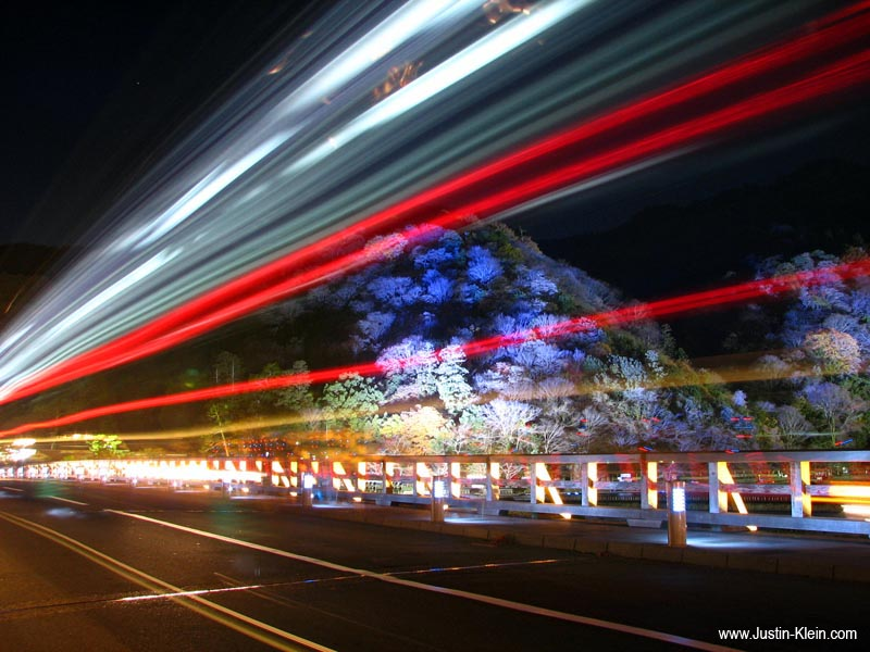 A city bus zooms by in front of an illuminated Arashiyama.