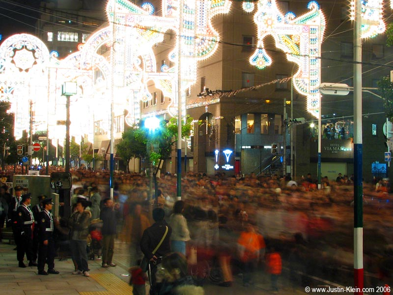 Crowds zoom by under the lights of Kobe's Luminarie Festival.