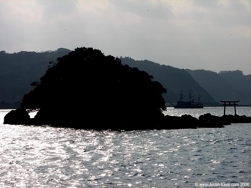 Off the coast of Shimoda, with a Black Ship replica visible in the distance.