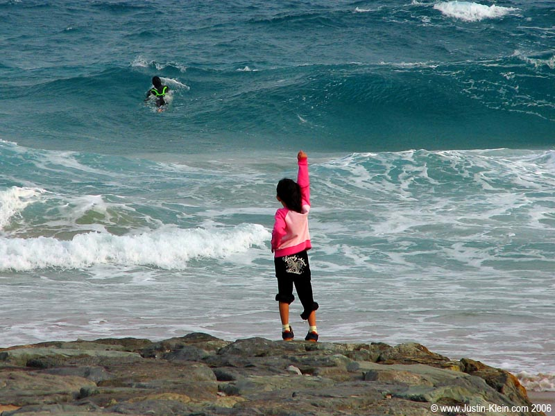 A little girl cheers on her father in the impossibly icy Shirahama waters.