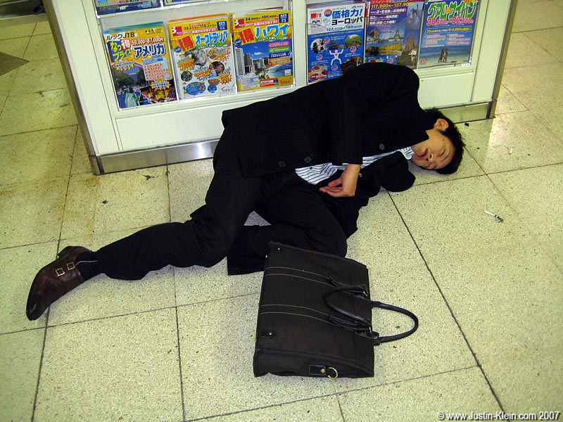 A passed-out salaryman on the floor of a trainstation.  Not at all an uncommon sight in Japan.  Lucky for him it's so safe here – no need to worry about that briefcase disappearing!