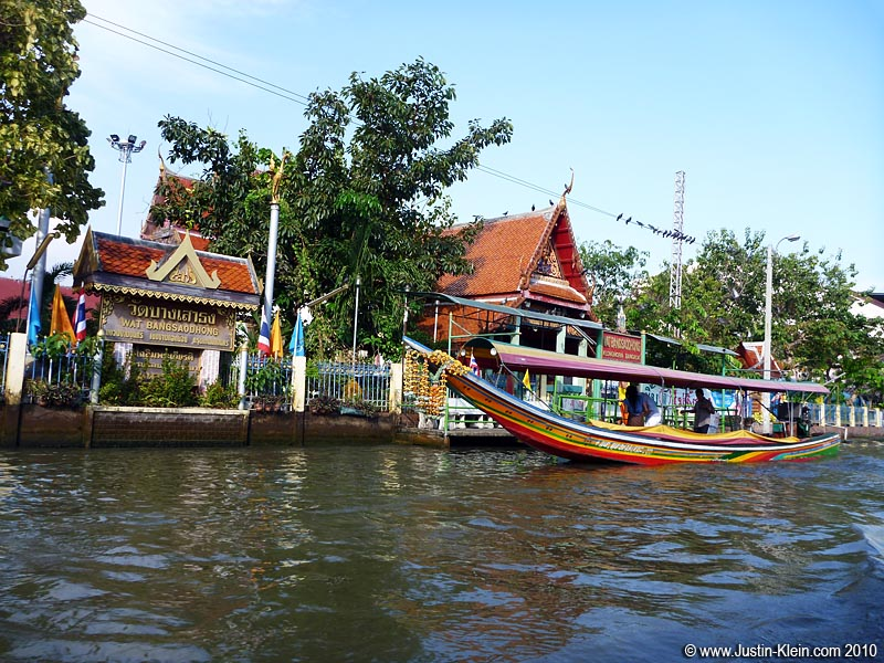 A water taxi stopping at a small temple.