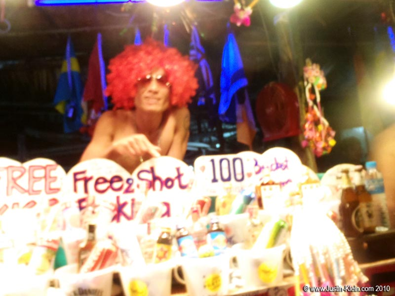 Down on the beach, competition to sell buckets is fierce.  This guy roped us in with his outrageous wig and promise of free extra shots.  He did not disappoint – even did one with us!