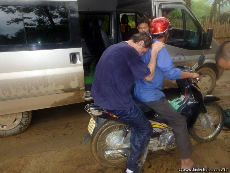 With his ankle now shattered, we carried my dad as far as we could – but for the last few dozen meters we had to put him on a bike.  The guy who'd brought us spare parts from the lodge helped drive him across one particularly deep pit of mud.