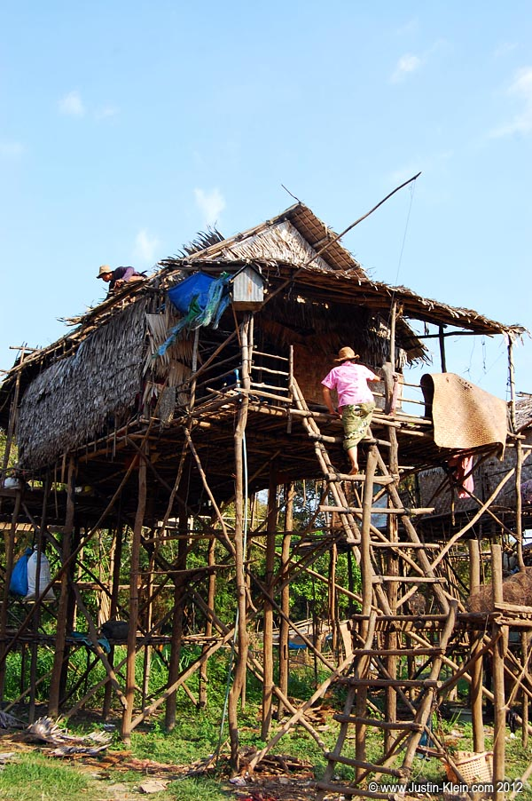 A woman climbs up to her house in the stilt village of Kampong Phluk.