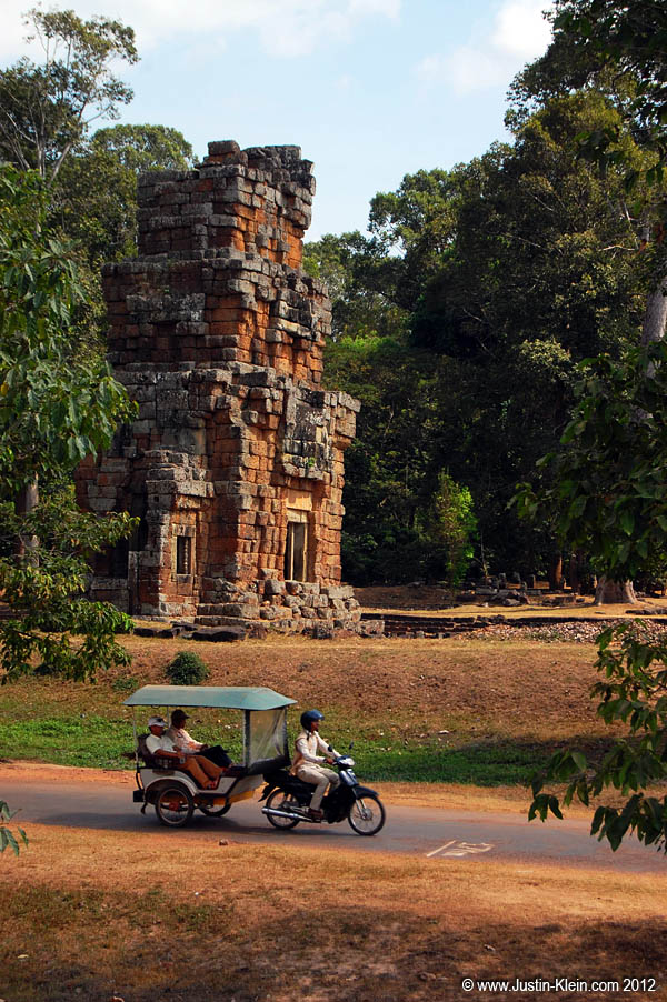 Tourists on a tuktuk inside Angkor Thom.  Tuktuk and tourbus are how the majority of visitors get around Angkor.
