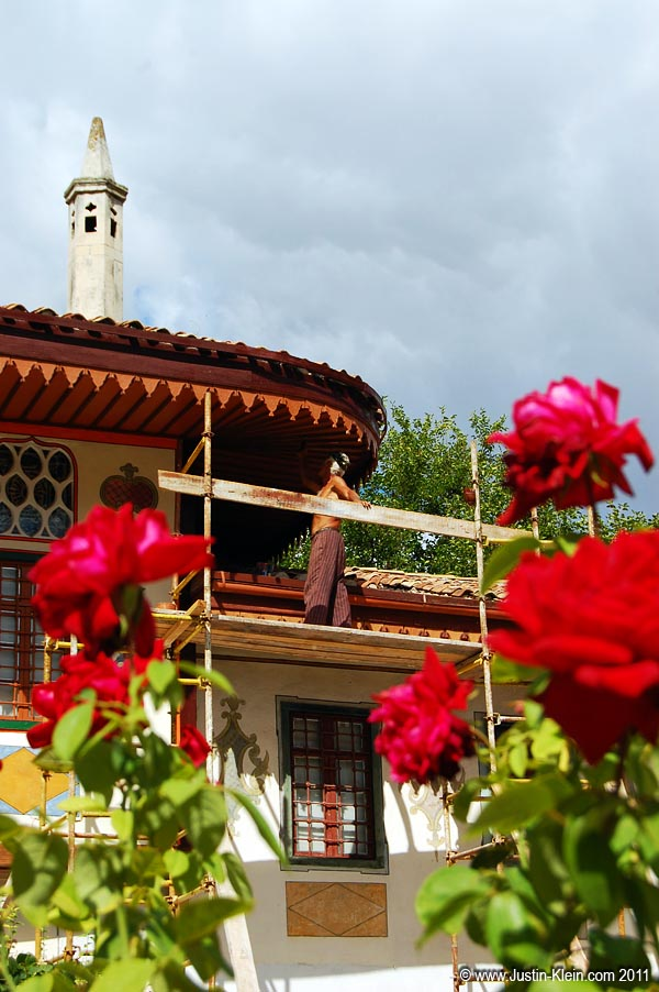 An old man applies a fresh coat of paint to Khan's Palace in Bahkchisaray, Ukraine.