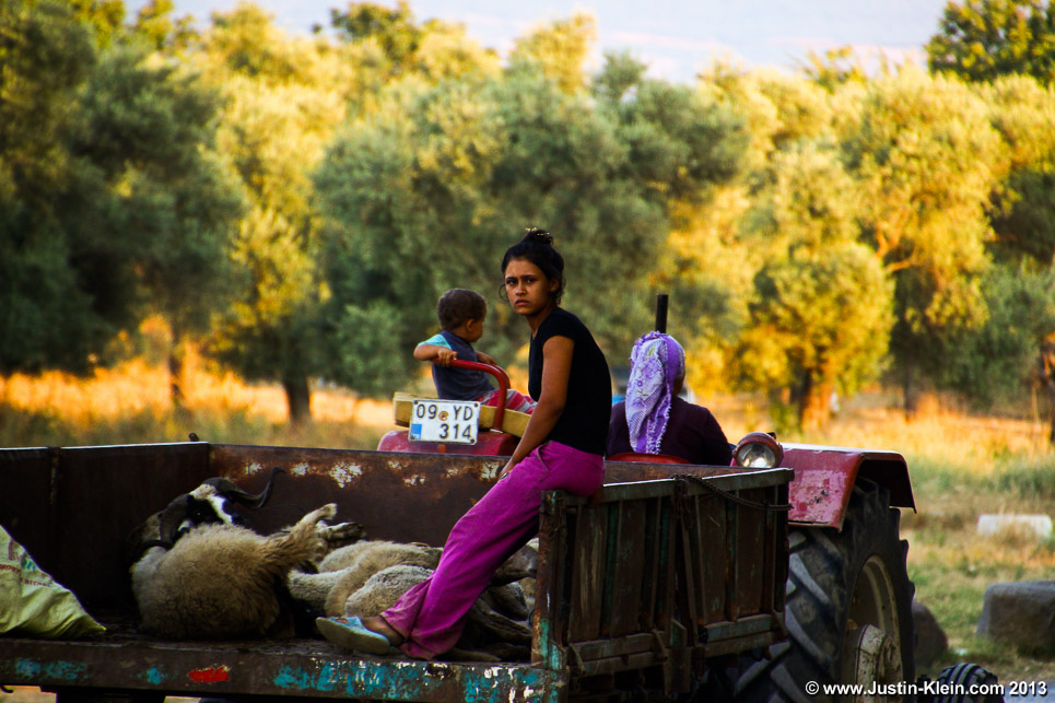 A young woman relaxes after helping her mother round up their sheep just outside the village of Balat, Western Turkey.
